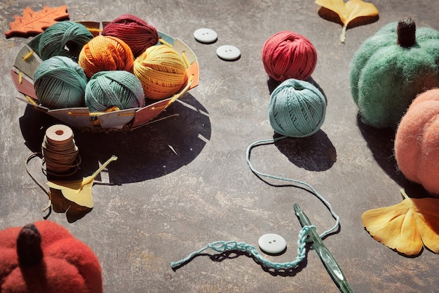 Garnknäuel, häkelnadel mit faden, dekorative filzkürbisse, ginkgoblätter