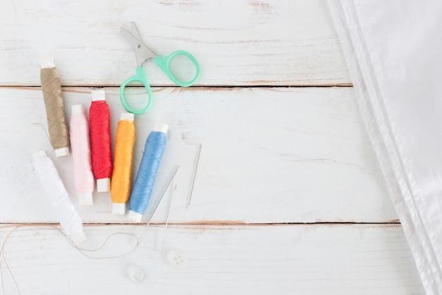 Garnrolle viele färben mit nadel und kleinen scheren auf weißem hölzernem brett