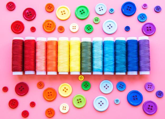 Garnrollen und knöpfe in den farben des regenbogens
