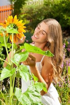 Gartenarbeit am sommer - glückliche frau mit sonne blüht in ihrem garten