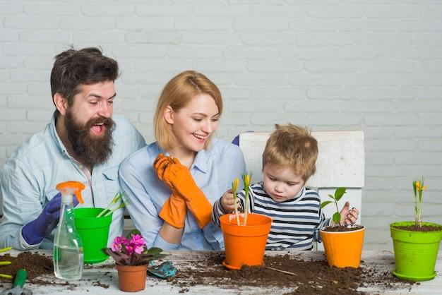 Gartenarbeit. familie verbringt zeit zusammen. pflanzen. familie, die blumen pflanzt. sich um pflanzen kümmern. gartenarbeit entdecken und lehren.