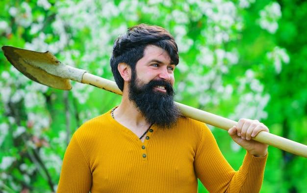 Gartenarbeit im frühling. bärtiger gärtner mit gartenarbeitsspaten. lächelnder mann, der sich zum pflanzen vorbereitet.
