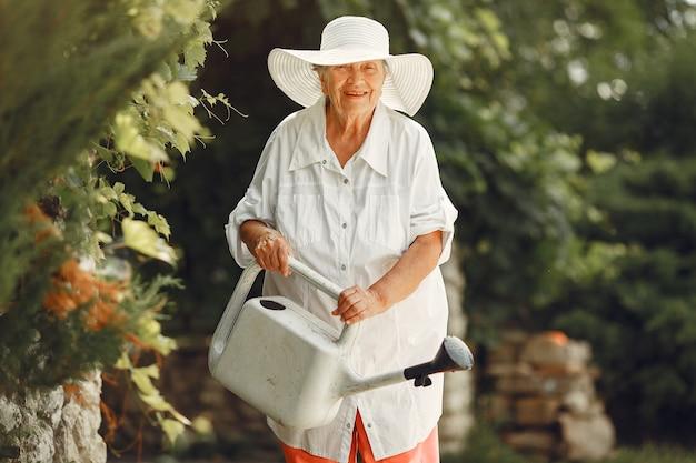 Gartenarbeit im sommer. frau, die blumen mit einer gießkanne wässert. alte frau, die einen hut trägt.