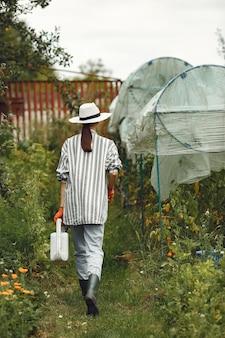 Gartenarbeit im sommer. frau, die blumen mit einer gießkanne wässert. mädchen, das einen hut trägt.