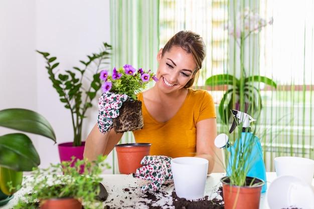 Gartenarbeit ist mehr als hobby. schöne hausfrau mit blume im topf und gartenset. pflege für eine topfpflanze