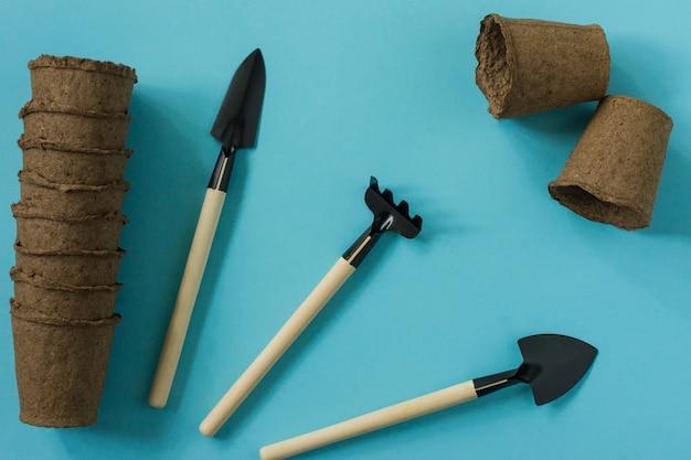 Gartenarbeit zu hause. anbau von lebensmitteln auf der fensterbank. werkzeuge, torftöpfe und gepresster boden für setzlinge. ansicht von oben. flatlay auf blauem hintergrund.