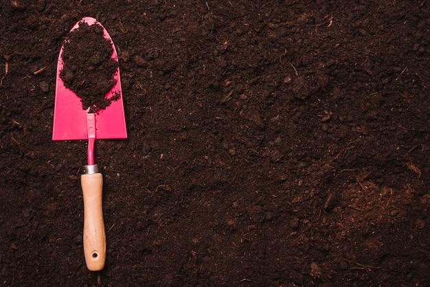 Gartenarbeitkonzept mit schaufel auf boden