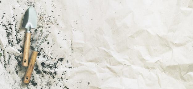 Gartenarbeitversorgungen auf zerknittertem papier mit kopienraum. umpflanzen, wiederbepflanzen,