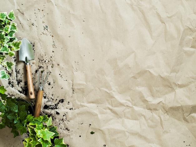 Gartenarbeitversorgungen mit anlagen in töpfen auf draufsicht des zerknitterten kraftpapiers