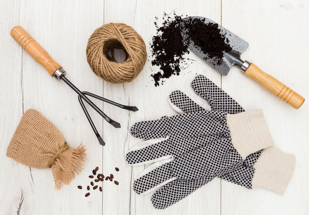 Gartenarbeitwerkzeuge der flachen lage auf hölzernem hintergrund