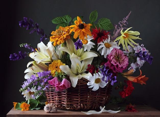 Gartenblumen im korb. stillleben mit blumenstrauß und muschel.