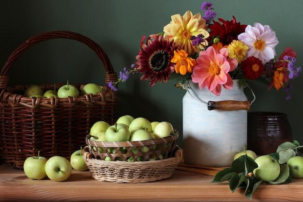 Gartenblumen und frühe grüne äpfel. stillleben mit einem strauß dahlien und früchten auf einem holztisch.