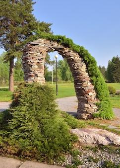 Gartenbogen aus steinen dekorativer landschaftsgarten unter blauem himmel im frühling