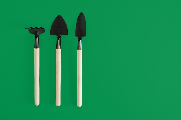 Gartengeräte auf grünem hintergrund. garedeining-konzept kleine schaufeln und rechen zum pflanzen von setzlingen und zimmerpflanzen