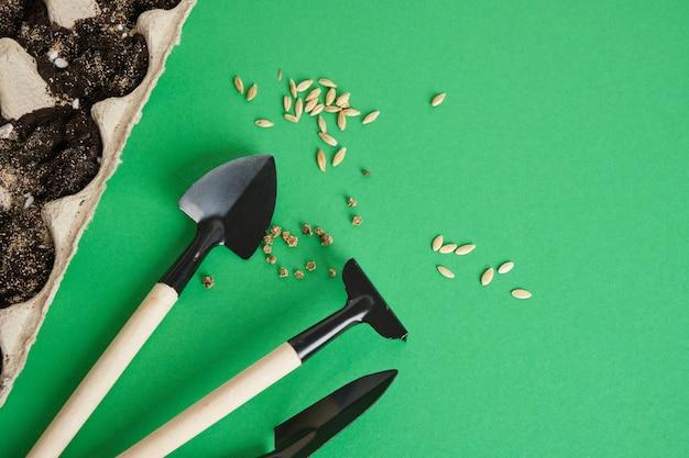 Gartengeräte auf grünem hintergrund. kleine schaufeln und rechen zum pflanzen von setzlingen und zimmerpflanzen, umweltfreundliches gartenkonzept