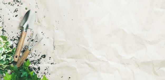 Gartengeräte mit efeu in töpfen auf kraftpapier mit textfreiraum.