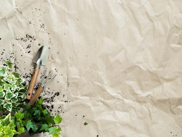 Gartengeräte mit pflanzen in töpfen auf draufsicht des zerknitterten kraftpapiers