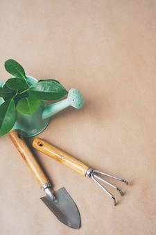 Gartengeräte, papiertöpfe, gießkanne auf kraftpapier mit textfreiraum. vom topf zum garten.