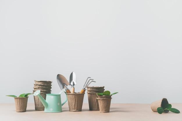 Gartengeräte, papiertöpfe, gießkanne auf kraftpapier