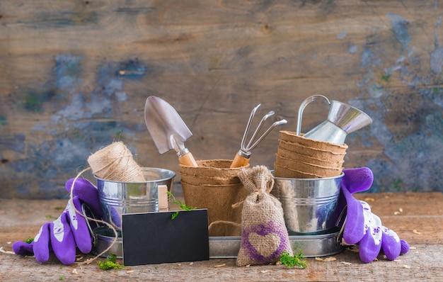 Gartengeräte, töpfe und utensilien auf rustikalem holzhintergrund, mit einer kreidetafel