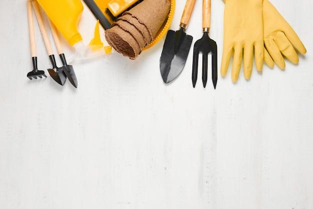 Gartengeräte und ausrüstung auf weißem holztisch