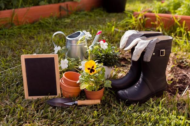 Gartengeräte und blumen auf dem boden mit leerer tafel