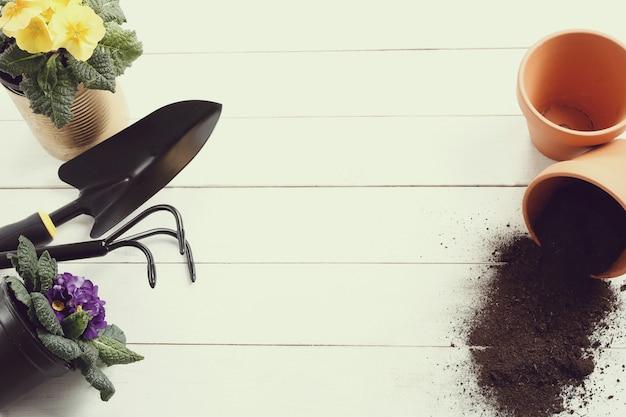 Gartengeräte und blumentopf auf hölzernem hintergrund