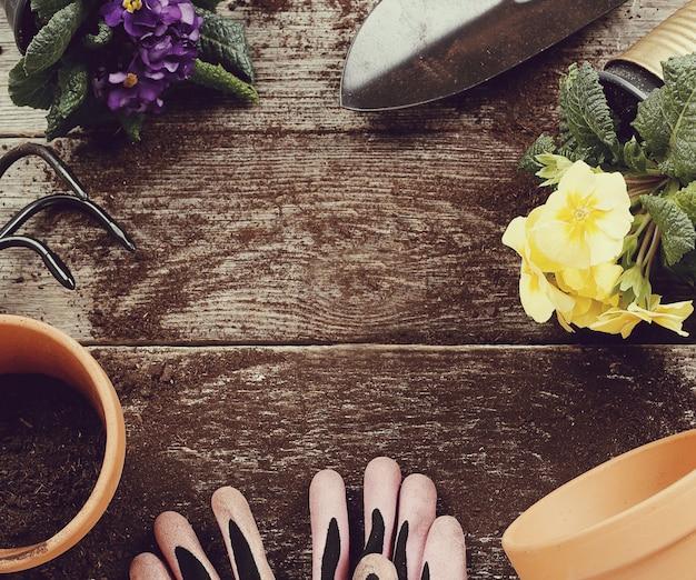 Gartengeräte und blumentopf auf hölzernem tischhintergrund