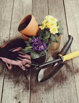 Gartengeräte und blumentopf auf holztisch