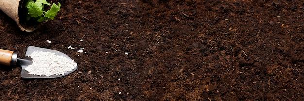 Gartenhintergrund. gartengeräte und pflanzen auf einem bodenhintergrund mit kopierraum für text. frühlingsarbeiten, draufsicht mit freiem textraum. banner, plakat