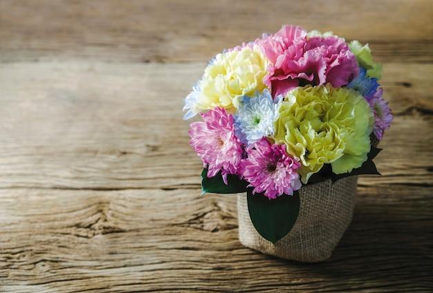 Gartennelken- und chrysanthemenblumen im topf auf altem holz zu hause