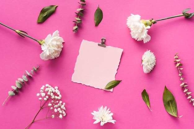 Gartennelkenblumen mit blatt des leeren papiers auf tabelle