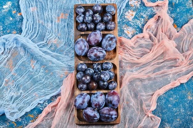 Gartenpflaumen auf holzplatte und auf blauer oberfläche mit tischdecken.