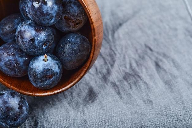Gartenpflaumen auf schüssel auf grauer tischdecke.