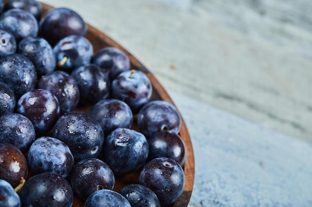 Gartenpflaumen in einer platte auf einem blauen hintergrund. hochwertiges foto
