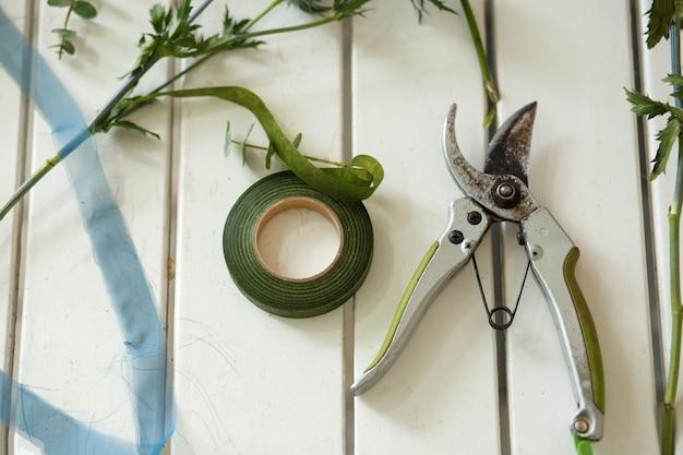 Gartenschere und andere floristenwerkzeuge und cutted frische blumen, die auf weißem holztisch liegen