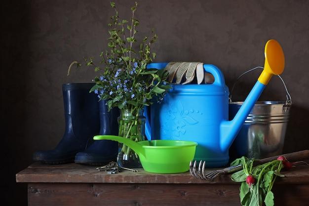 Gartenstilleben mit strauß, gießkanne und gummistiefeln.
