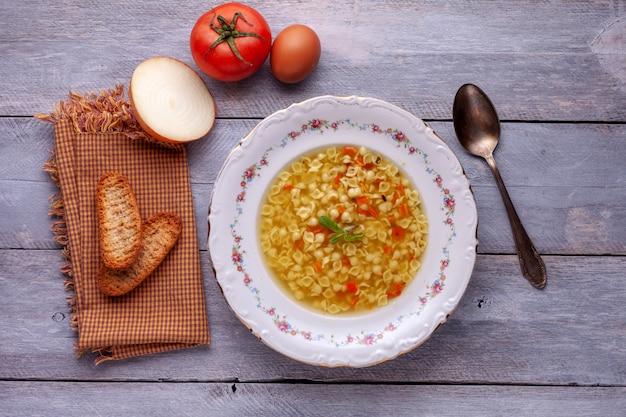 Gartensuppe in porzellanteller, tomate, zwiebel, ei und metalllöffel.