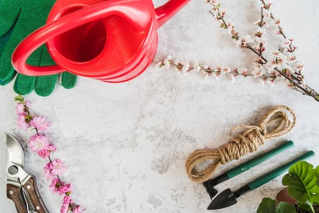 Gartenwerkzeuge; gießkanne; handschuhe; blumenzweige; seil auf konkrete kulisse