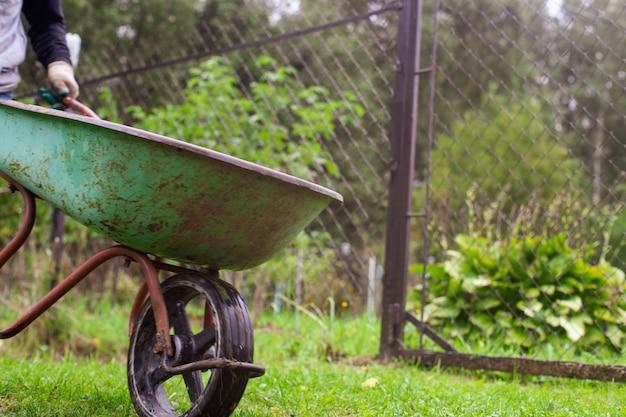 Gartenwerkzeuge. landwirtschaftliches konzept. saison der landwirtschaft. bauer mit schubkarre