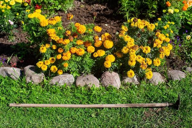 Gartenwerkzeuge. landwirtschaftliches konzept. saison der landwirtschaft. ein häcksler neben einem blumenbeet.