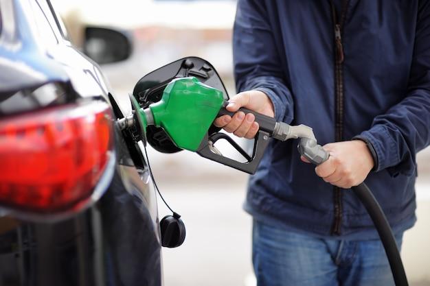 Gas an der gaspumpe pumpen. nahaufnahme des pumpenden benzinkraftstoffs des mannes im auto an der tankstelle.