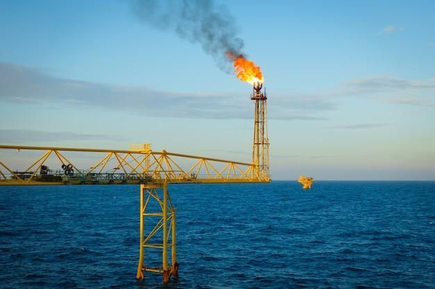 Gas wird von der fackelbrücke der offshore-gasplattform in die atmosphäre freigesetzt und verbrannt