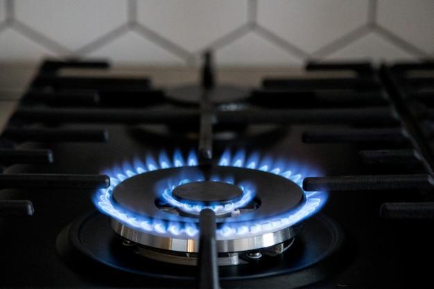 Gasbrenner auf schwarzem modernem küchenofen. küchengaskocher mit brennendem propangas.