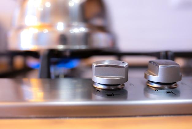 Gasherd in der küche einschalten. eine metallsilber-teekanne, die sich auf einem gas erwärmt.