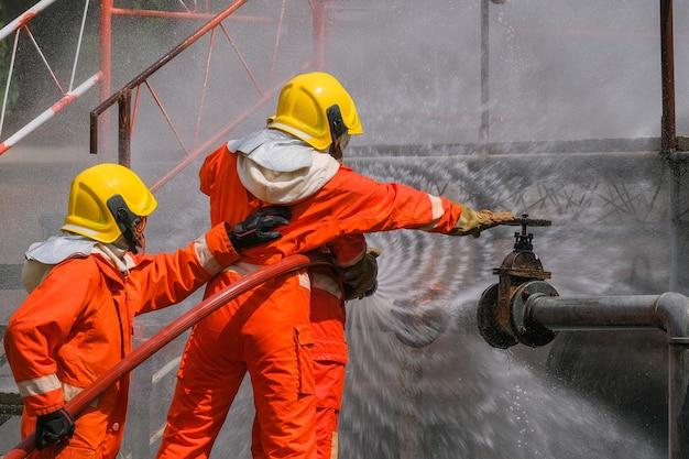 Gasleck aus rohr und ventilflamme aus gasleck. brandbekämpfung mit feuerlöschern und feuerlöschschlauch. feuerwehr im einsatz bei gasfeuer