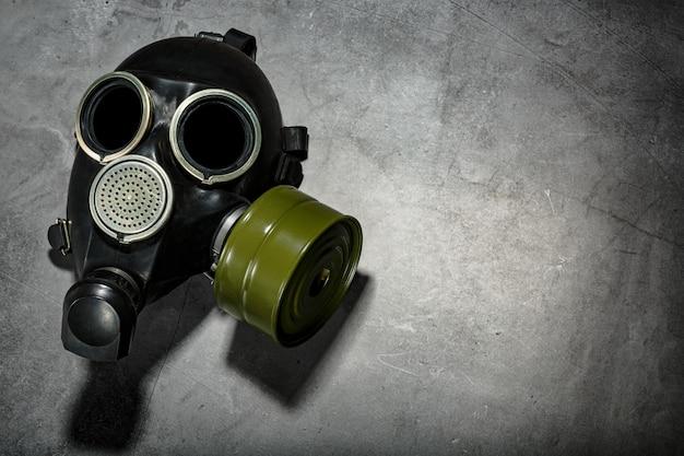 Gasmaske auf einem schwarzen steinhintergrund mit einer grünen filterpatrone. postapokalyptisches konzept.