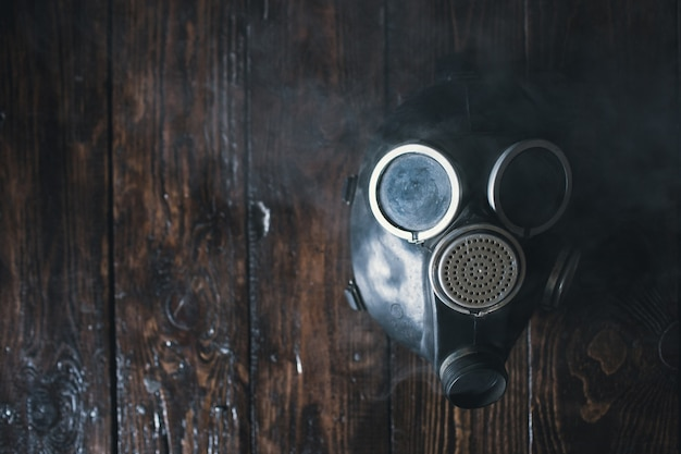 Gasmaske auf holzhintergrund. luftverschmutzung. natur umweltschutz. ökologische katastrophe. bio-gefahrenkonzept