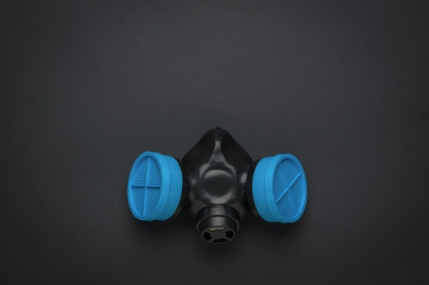 Gasmaske mit blauen filtern auf einer schwarzen oberfläche