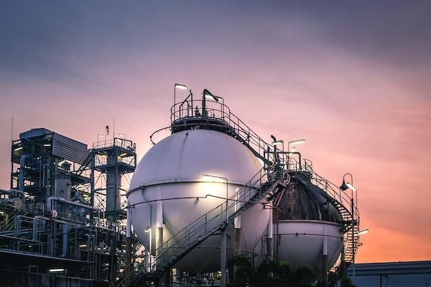 Gasspeicherkugeltanks in fabriken am sonnenuntergangshimmel